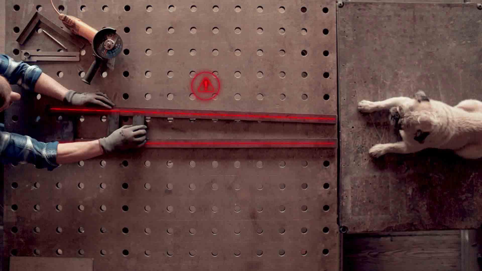 Das Bild zeigt eine Luftaufnahme von einer Werkbank. Auf dieser Werkbank liegt ein Mops. Vor dem Mops liegen zwei Eisenstangen. Beide Eisenstangen werden von zwei Händen gehalten. Sie sind durch Animation rot unmarkiert. Oberhalb der beiden Eisenstangen schwebt auch durch Animation ein runder Kreis in dem sich ein Dreieck mit einem Ausrufezeichen als Warnung befindet. Das Bild dient als Sliderbild für den Portfolioeintrag ifm Positionssensor von Panda Pictures.