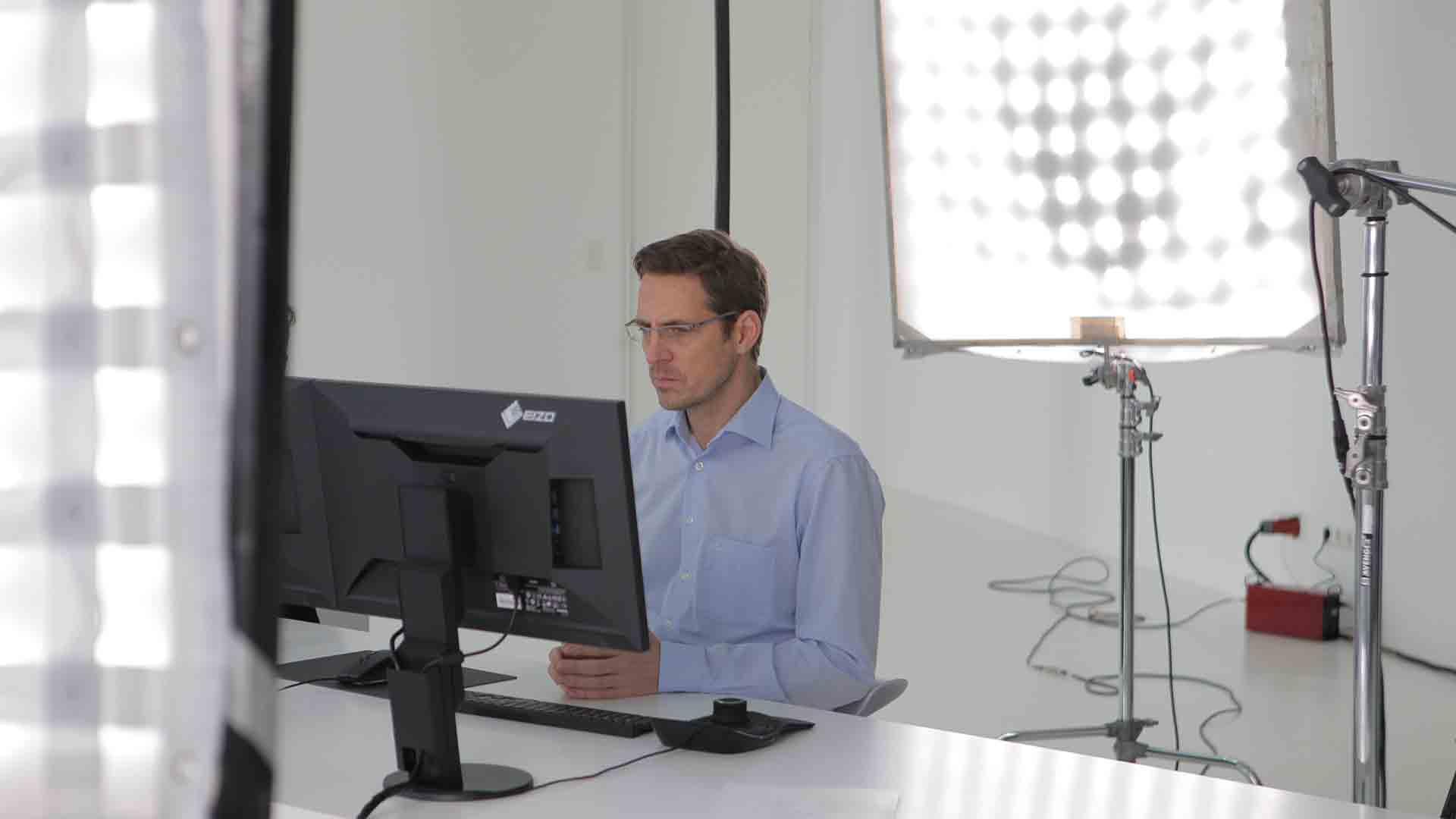 Das Bild zeigt einen Mann der an einem Schreibtisch sitzt. Er befindet sich an einem Filmset. Hinter und vor ihm sind zwei Lichtnetze aufgestellt. Auf dem Schreibtisch vor ihm stehen ein Computerbildschirm, eine Tastatur und eine Computermaus. Das Bild dient als Sliderbild für den Portfolioeintrag 3Dconnexion SpaceMouse von Panda Pictures.