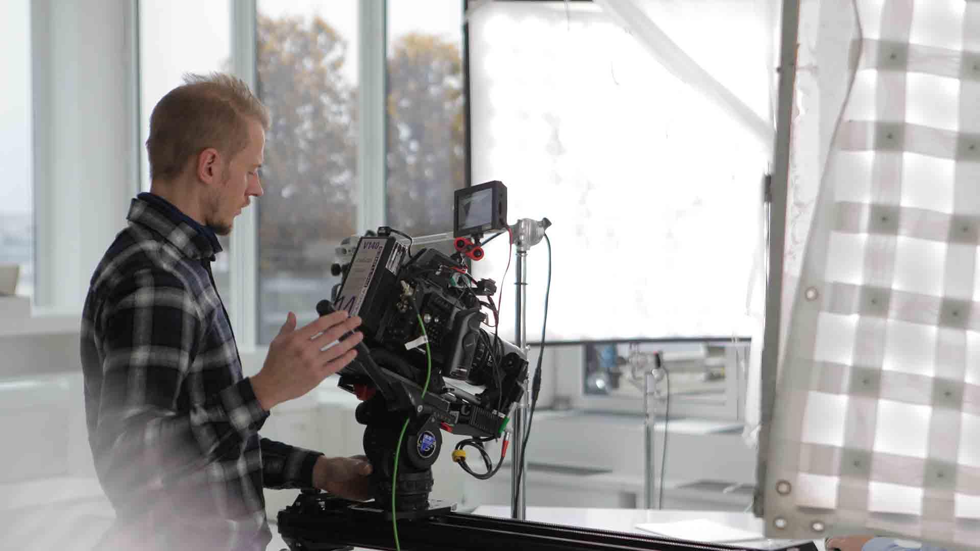 Das Bild zeigt einen Mann der vor einer Kamera steht. Er hält diese in seinen Händen und führt sie. Vor ihm ist ein Lichtnetz zu sehen. Das Bild dient als Sliderbild für den Portfolioeintrag 3Dconnexion SpaceMouse von Panda Pictures.