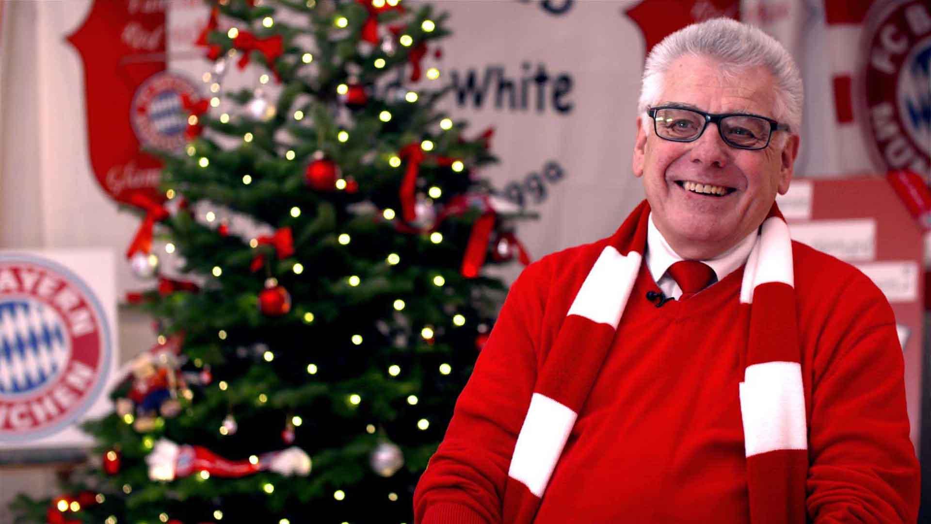 Das Bild zeigt einen Mann. Er sitzt vor einem geschmückten Tannenbaum. Um seinen Hals hängt ein rot-weißer Schal. Dieser ist ein Fanschal des FC Bayern Münchens. Er trägt außerdem einen roten Pullover und eine schwarze eckige Brille. Das Bild dient als Sliderbild für den Portfolioeintrag Audi | FC Bayern München Ehrenrunde von Panda Pictures.