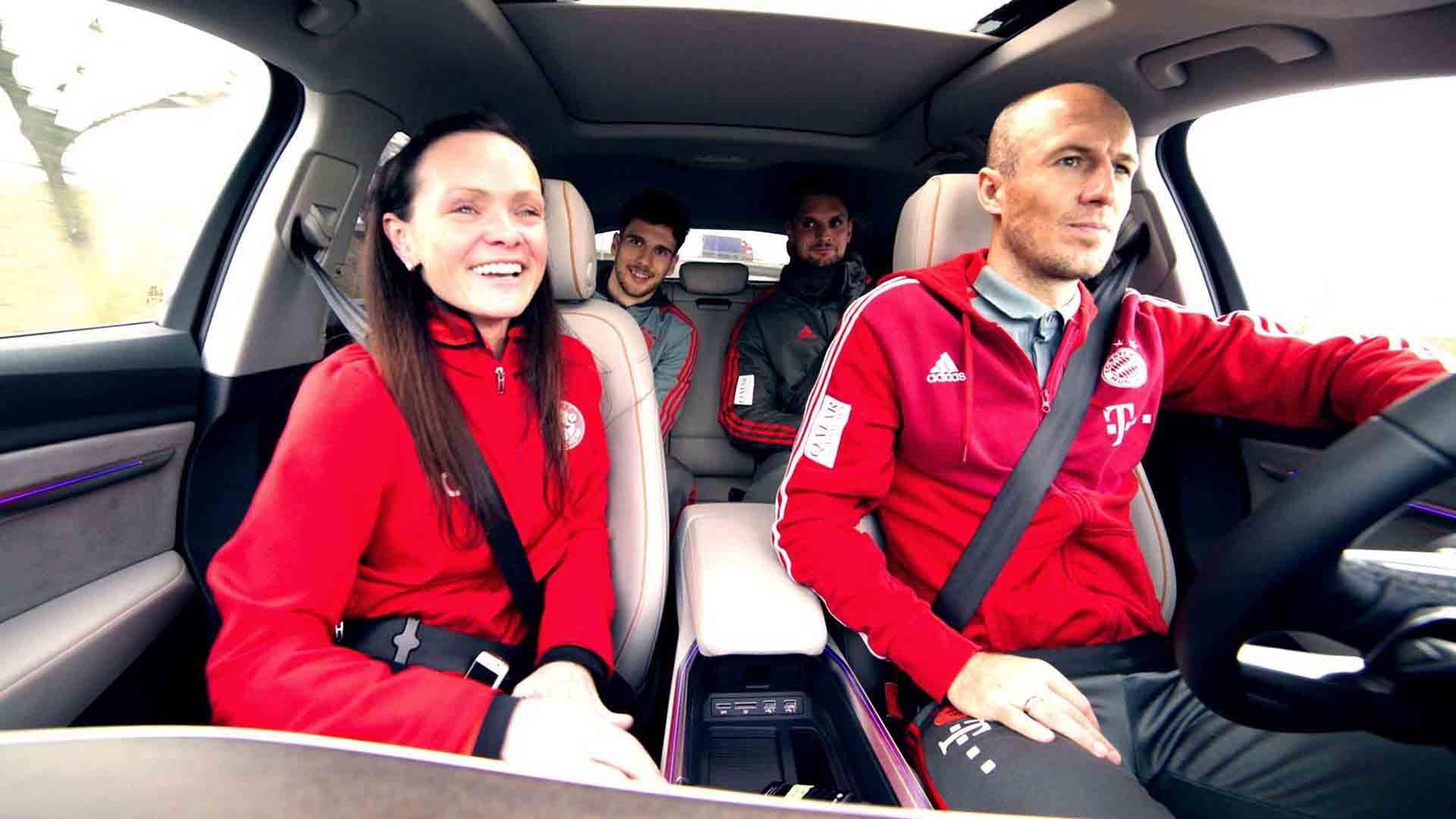 Das Bild zeigt ein Auto in dem vier Menschen sitzen. Bei diesen Menschen handelt es sich um FC Bayern München Stars und eine Trainerin einer Bambini Mannschaft. Der Mann der am Steuer sitzt ist Arjen Robben. Neben ihm sitzt Claudia Auner, sie ist Trainerin einer Bambini Mannschaft. Auf der Rückbank sitzen Leon Goretzka und Sven Ulreich. Das Bild dient als Sliderbild für den Portfolioeintrag Audi | FC Bayern München Ehrenrunde von Panda Pictures.