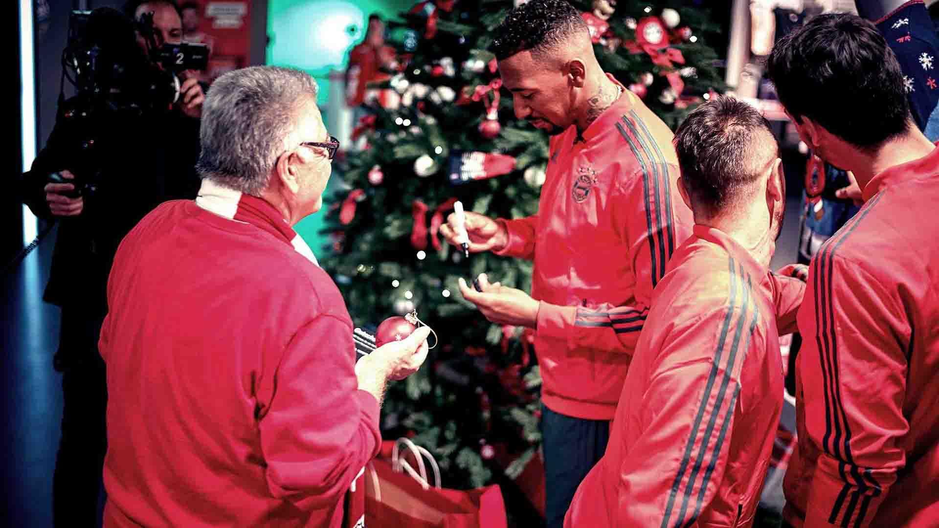 Das Bild zeigt vier Männer die vor einem Tannenbaum stehen. In der Mitte steht der FCB Star Jérôme Boateng. Er hält eine Christbaumkugel in der Hand und unterschreibt diese. Neben ihm auf der linken Seite steht ein Mann, der einen roten Pullover trägt. Rechts von ihm stehen zwei weitere Stars des FC Bayern Münchens. Das Bild dient als Sliderbild für den Portfolioeintrag Audi | FC Bayern München Ehrenrunde von Panda Pictures.