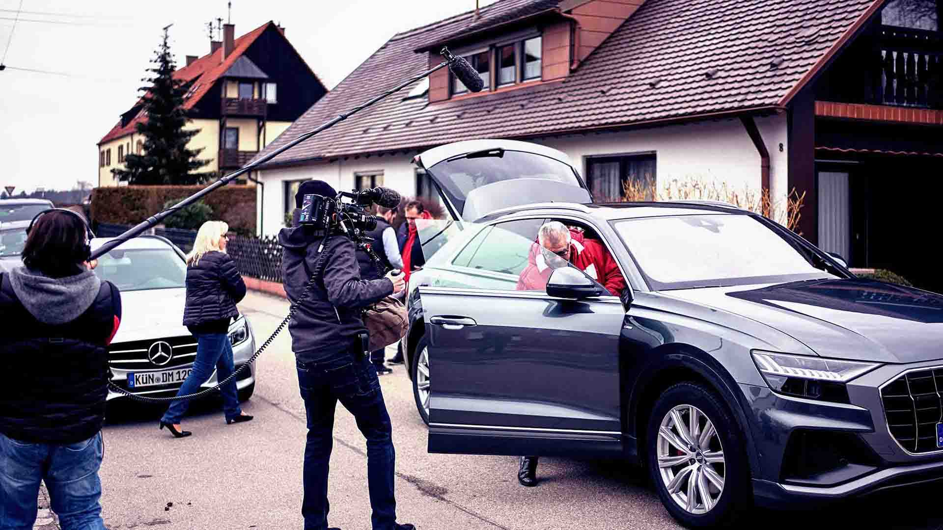 Das Bild zeigt ein parkendes Auto, das vor einem Haus steht. Aus dem Auto steigt ein Mann aus. Dieser wird von einem Kamerateam begleitet welches ihn filmt. Das Team läuft um das Auto herum. Das Bild dient als Sliderbild für den Portfolioeintrag Audi | FC Bayern München Ehrenrunde von Panda Pictures.