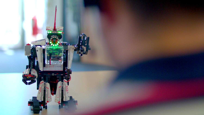 """Das Bild zeigt einen verschwommenen Menschen der vor einem Roboter steht. Er hebt seine rechte Hand in die Höhe. Aus seinem Kopf ragt eine rote Antenne heraus. Sein Körper sieht so aus, als sei er durch Lego zusammengebaut worden. Das Bild dient als Sliderbild für den Portfolioeintrag """"Bayrisches Staatsministerium - Innovationspreis Bayern"""" von Panda Pictures."""