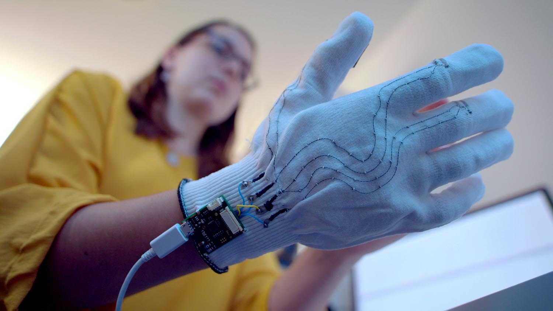 Das Bild zeigt eine Frau die einen weißen Handschuh trägt. Aus diesem Handschuh laufen Kabel heraus. Der Hintergrund ist verschwommen, man erkennt ein Tablet. Das Bild dient als Sliderbild für den Portfolioeintrag Bayrisches Staatsministerium - Innovationspreis Bayern von Panda Pictures.
