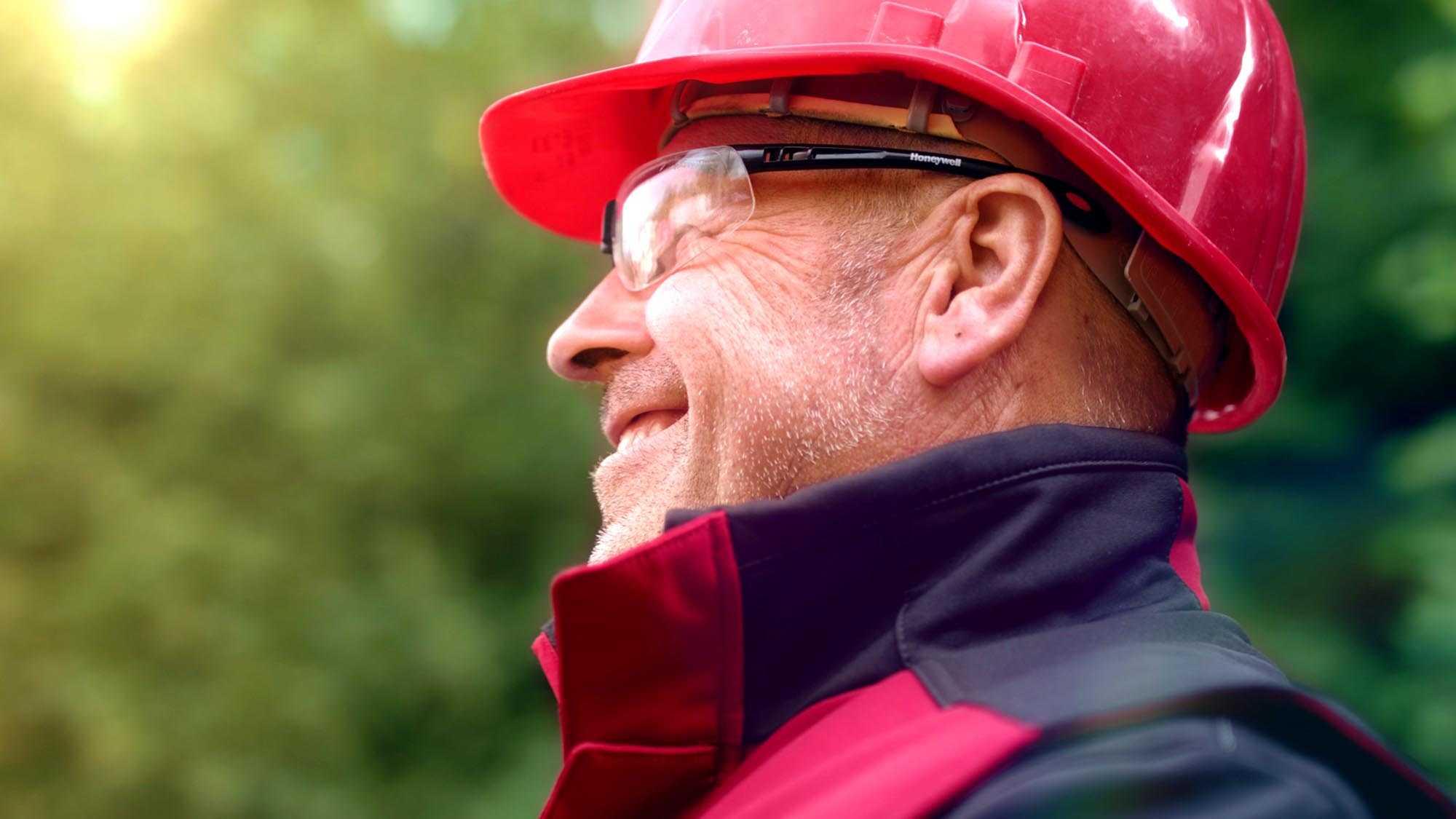 Das Bild zeigt einen lachenden Mann der vor einer Hecke steht. Die Hecke ist etwas verschwommen. Der Mann trägt einen roten Schutzhelm und eine Schutzbrille. Seine Jacke ist rot. Sein Blick ist nach links, Richtung Himmel gerichtet. Das Bild dient als Making Of Bild für den Portfoliobeitrag Peri Produktfilme von Panda Pictures.