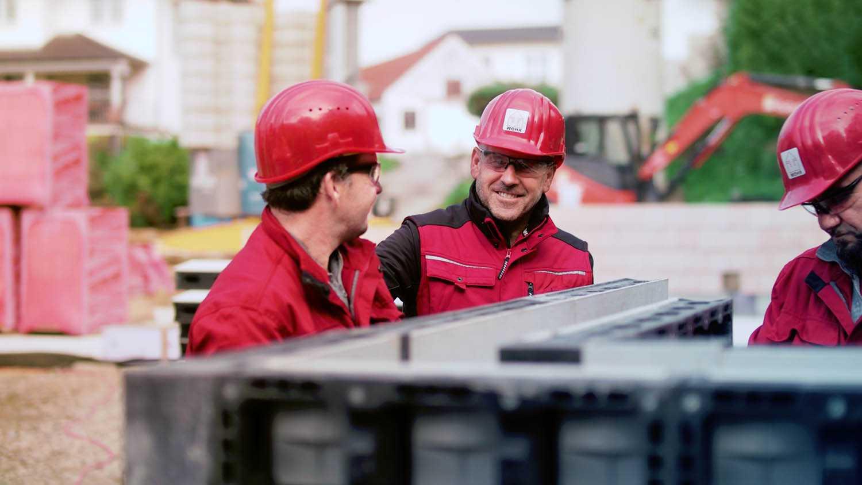 Das Bild zeigt drei Männer in roten Jacken. Sie tragen Schutzhelme und Schutzbrillen. Sie stehen auf einer Baustelle und schauen sich an. Sie unterhalten sich. Das Bild dient als Sliderbild für den Portfoliobeitrag Peri Produktfilme von Panda Pictures.