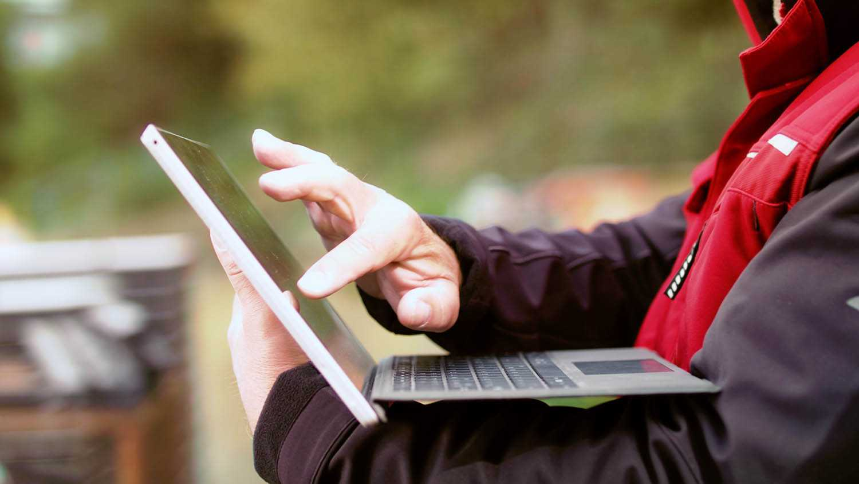 Das Bild zeigt einen Mann. Man sieht seinen Oberkörper. Er hält ein silbernes Tablet in seiner linken Armbeuge. Er berührt den Bildschirm mit seiner rechten Hand. Das Bild dient als Sliderbild für den Portfolioeintrag Peri Produktfilme von Panda Pictures.
