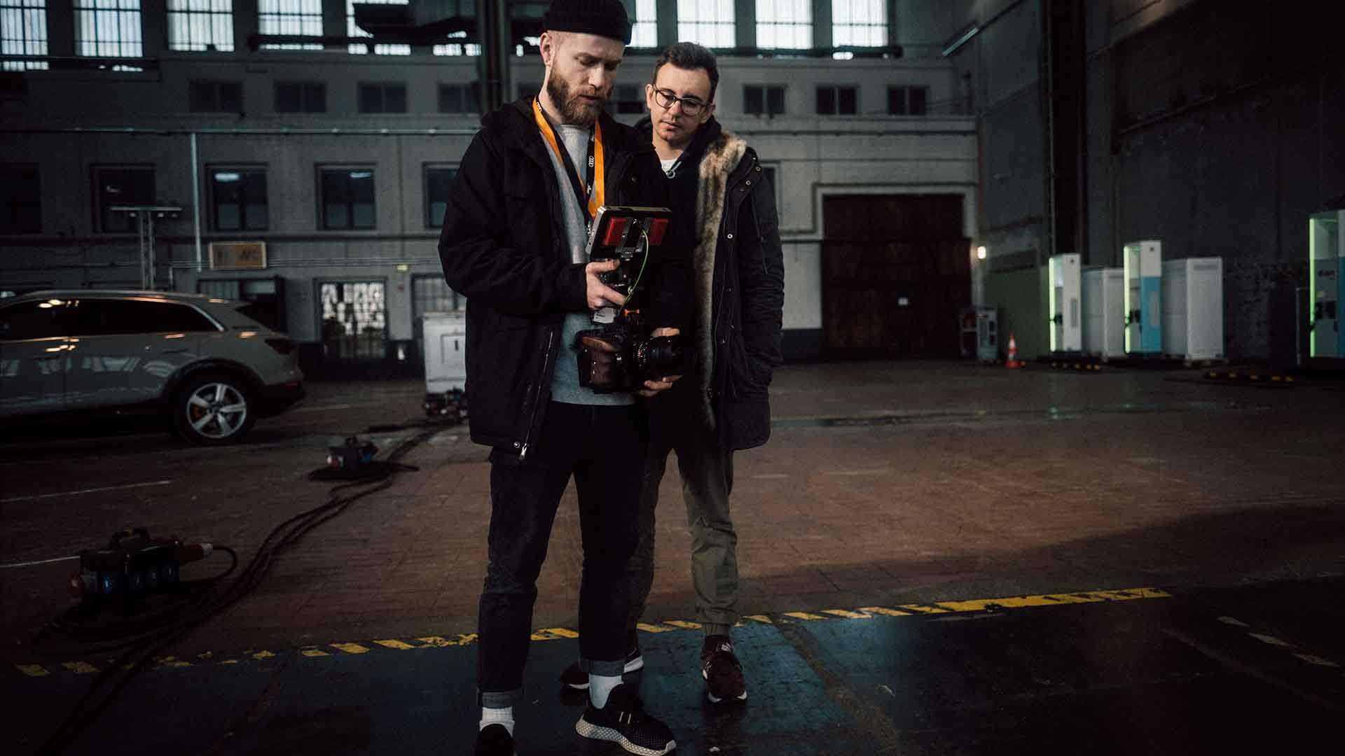 Das Bild zeigt zwei Männer, die ein Gespräch miteinander führen. Der Mann auf der linken Seite hält eine Kamera in seinen Händen. Der Mann auf der rechten Seite schaut dem Mann mit der Kamera über die Schulter direkt in den Monitor der Kamera. Beide stehen in einer Garage. Das Bild dient als Sliderbild für den Portfolioeintrag Audi | Electrifying Berlinale von Panda Pictures.