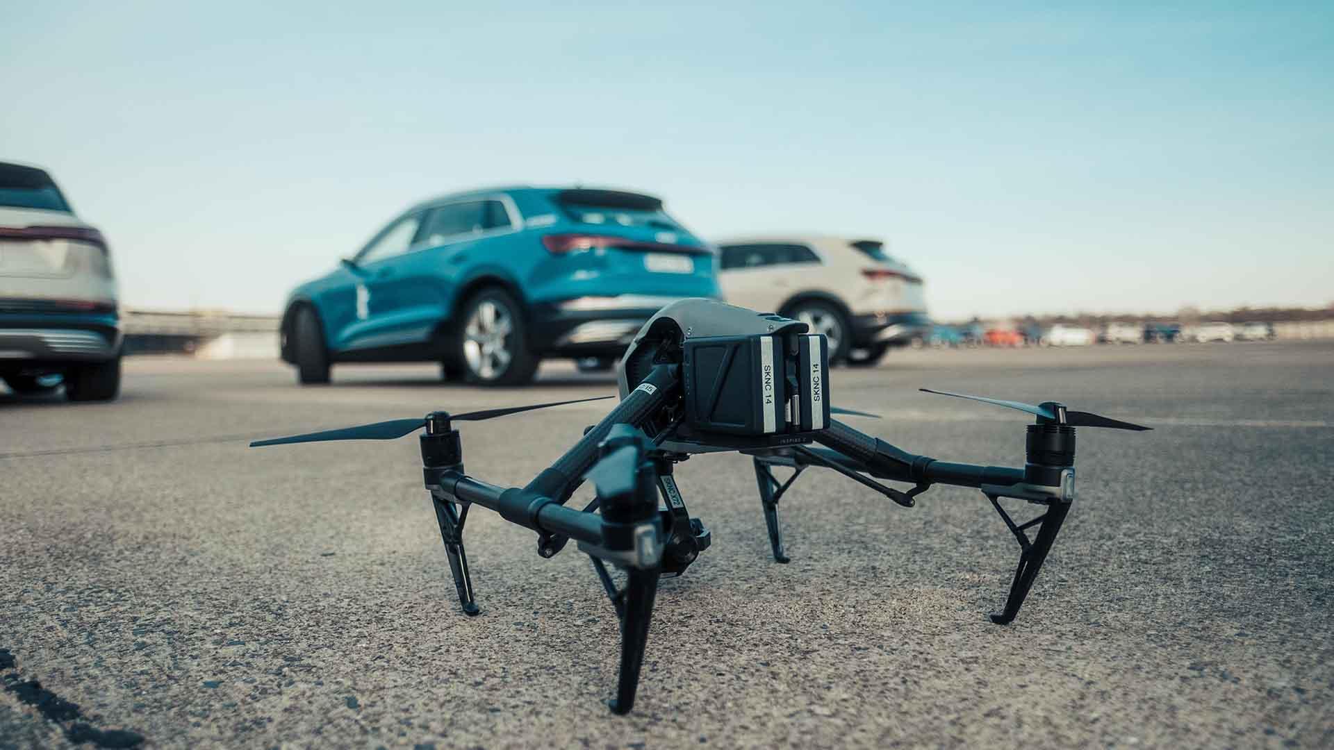 Das Bild zeigt eine Drohne. Die Drohne ist schwarz und steht auf einer Straße. Hinter der Drohne stehen drei Autos. Die Drohne steht im Fokus, da diese scharf zu erkennen ist. Die Autos sind unscharf, man erkennt jedoch dass essen ich um Fahrzeuge der Marke Audi handelt. Bei den Modellen handelt es sich um die Fahrzeugreihe e-tron. Das Bild dient als Sliderbild für den Portfolioeintrag Audi | Electrifying Berlinale von Panda Pictures.