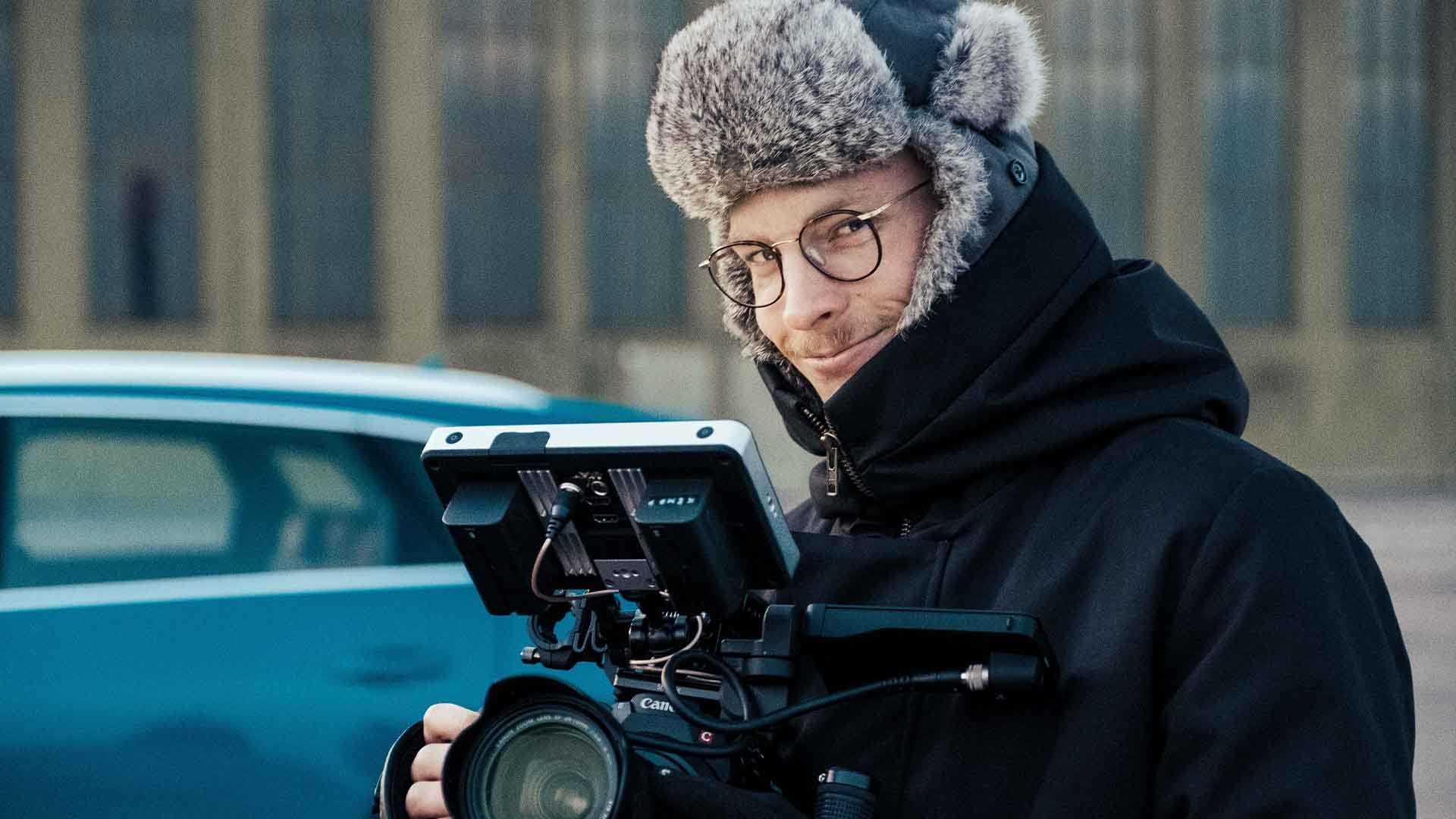 Das Bild zeigt einen Mann. Dieser Mann hält eine Kamera in den Händen. Der Mann trägt eine Brille und eine Mütze. Hinter ihm ist ein blaues Fahrzeug zu erkennen. Er lächelt. Das Bild dient als Sliderbild für den Portfolioeintrag Audi | Electrifying Berlinale von Panda Pictures.