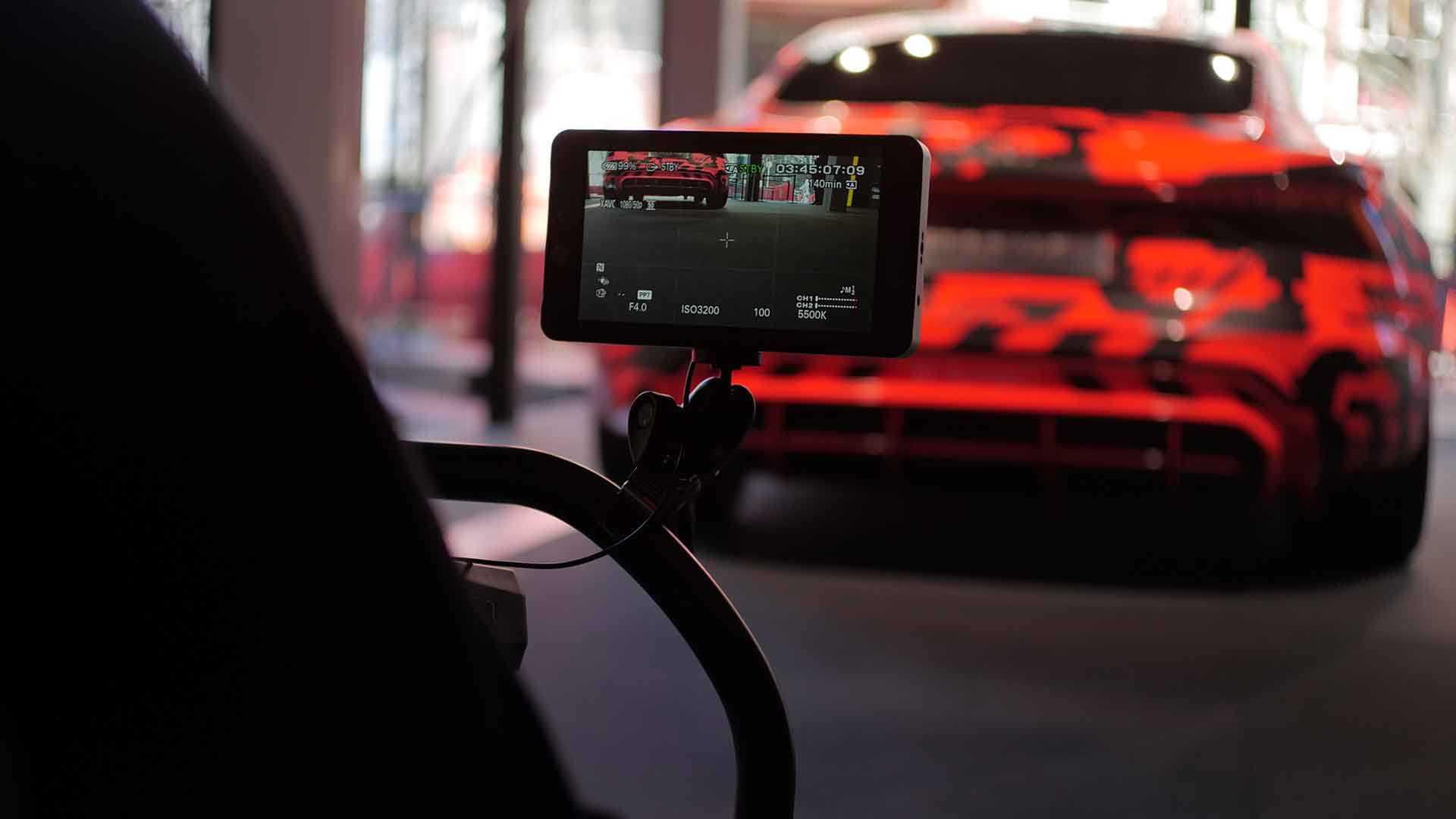 Das Bild zeigt ein rot-schwarz gemustertes Auto. Zu sehen ist nur die Hinteransicht des Autos. Das Auto wird über einen Monitor, der an einem Kamerastab hängt, gezeigt. Der Monitor ist das Zentrum des Bildes, er ist scharf zu sehen. Hinter dem Monitor ist das Auto unscharf zu erkennen. Das Bild dient als Sliderbild für den Portfolioeintrag Audi | Electrifying Berlinale von Panda Pictures.