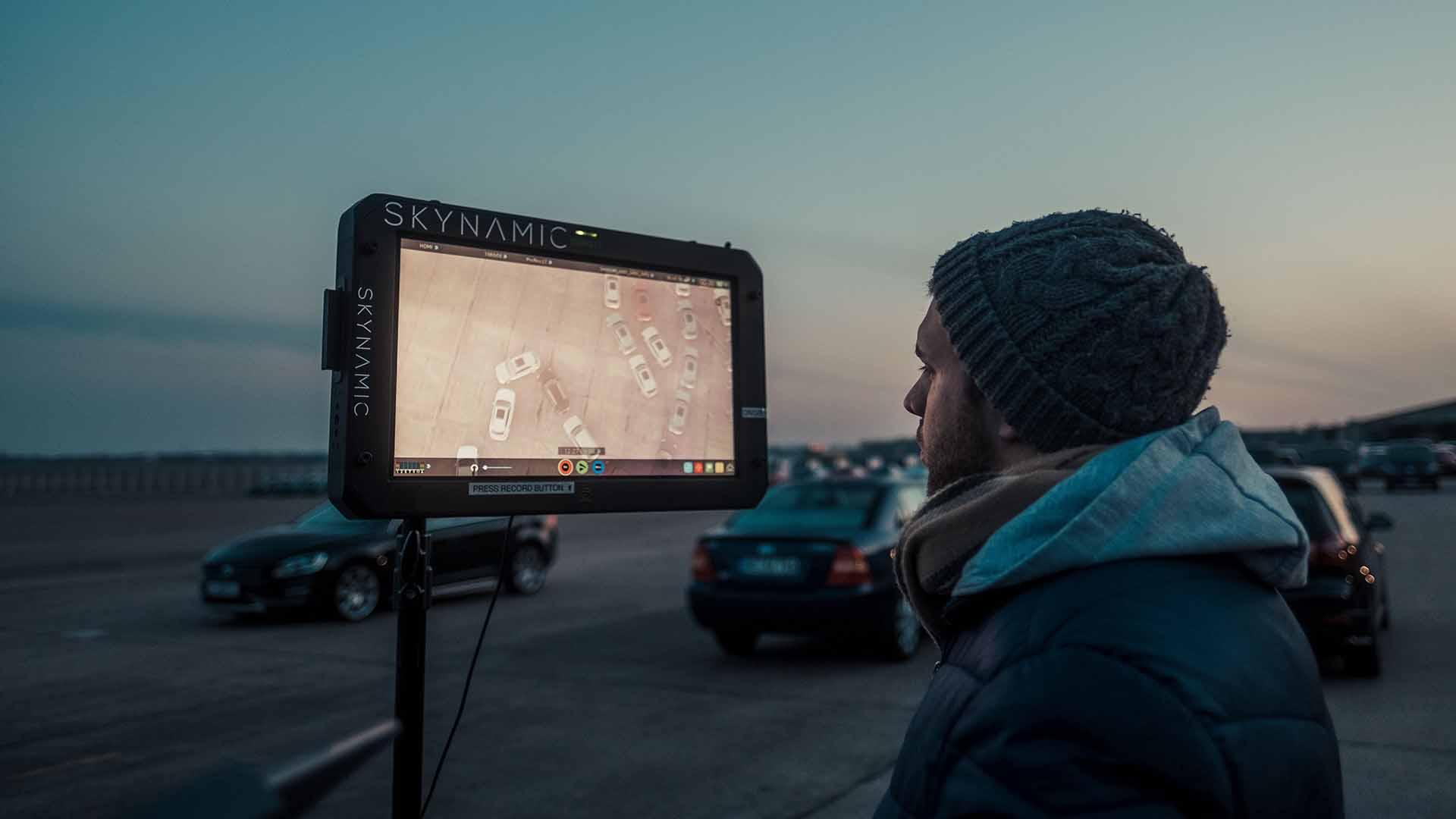 Das Bild zeigt einen Monitor auf dem viele Audi e-trons herumfahren. Vor dem Bildschirm steht ein Mann, der diesen konzentriert beobachtet. Er trägt eine Mütze. Hinter dem Monitor sieht man die Autos, die auf diesem abgebildet werden, herumfahren. Das Bild dient als Sliderbild für den Portfolioeintrag Audi | Electrifying Berlinale von Panda Pictures.