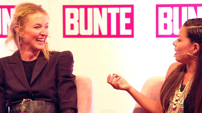 Das Bild zeigt zwei Frauen. Sie sind dabei sich zu unterhalten. Beide tragen Mikrofone. Sie sitzen auf rosa Sesseln vor einer Wand. Die Wand ist weiß und auf ihr ist das Logo Bunte zu sehen. Das Bild dient als Sliderbild für den Portfolioeintrag Reviderm Beauty Days von Panda Pictures.