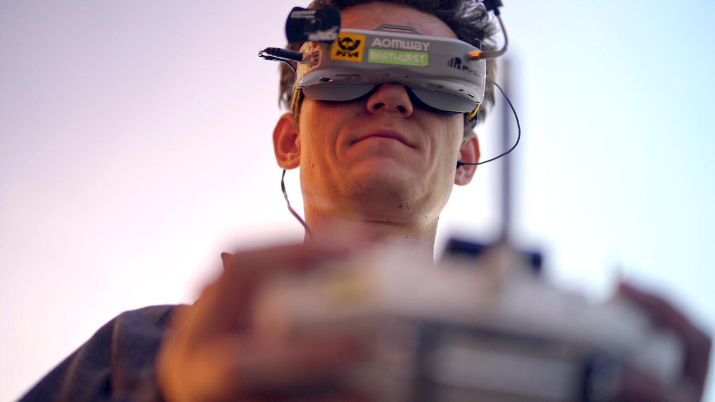 Das Bild zeigt einen Mann der eine VR Brille trägt. Dadurch sieht man seine Augen nicht. Die Brille trägt die Farbe silber. Er hält etwas in der Hand, man erkennt jedoch nicht was, da es verschwommen ist. Das Bild dient als Making Of Bild für den Portfolioeintrag WERK1 Drone Race von Panda Pictures.