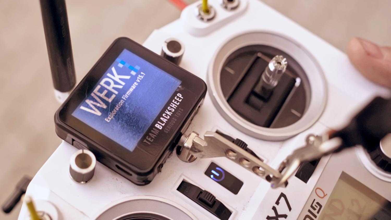 Das Bild zeigt eine Steuerung die für eine Drohne zuständig ist. Die Steuerung trägt die Farbe weiß. Auf ihr sieht man einen Monitor, dieser ist ziemlich klein. Er trägt die Worte Werk1. Unterhalb des Monitors sind noch die Worte Blacksheep zu sehen. Das Bild dient als Sliderbild des Portfolioeintrags WERK1 Drone Race von Panda Pictures.