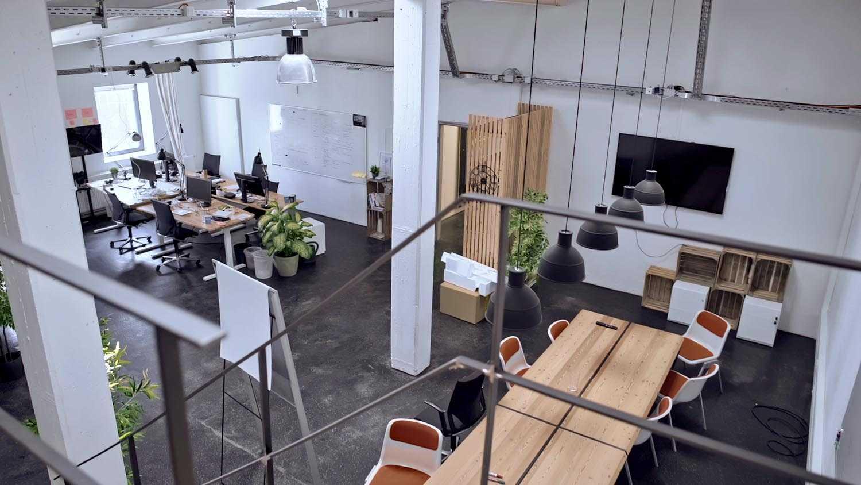 Das Bild zeigt einen großen Raum der als Büro genutzt wird. Das Bild wurde von einer etwas erhöhten Treppe, die im selben Raum steht, aufgenommen. Man erkennt einige Treppengeländer. Die Rechte Seite des Raumes ist mit einem Arbeitsplatz ausgefüllt, es stehen Schreibtische mit Computerbildschirmen und eine Flipchart herum. Die rechte Seite des Raumes ist mit einem Holztisch ausgefüllt. Von der Decke hängen schwarze Leuchten über diesem Tisch. Er ist aus Holz. Diverse Pflanzen füllen den Raum zusätzlich. Das Bild dient als Sliderbild für den Portfolioeintrag WERK1 Drone Race von Panda Pictures.