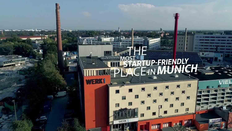 """Das Bild zeigt das Werk1, ein Gebäude, welches in München steht. Auf der linken Seite des Gebäudes sind die Worte Werk 1 zu lesen. Hinter dem Gebäude stehen zwei Türme, sie tragen beide die Farbe ziegelrot. Auf dem Dach des Gebäudes steht der animierte Text """"The most startup friendly place in Munich"""". Hinter dem Werk1 sind weitere Gebäude zu sehen. Am Horizont stehen Bäume. Das ganze Bild wurde aus der Luft aufgenommen. Das Bild dient als Sliderbild für den Portfolioeintrag WERK1 Drone Race von Panda Pictures."""