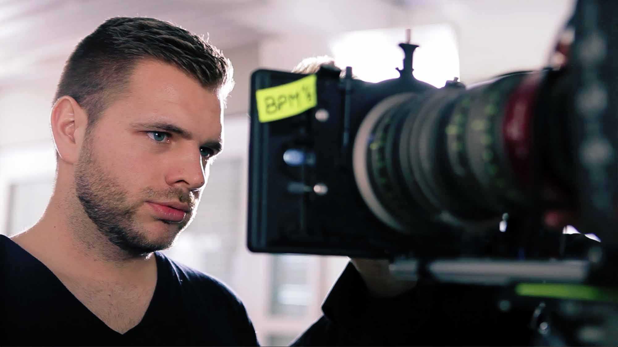 Das Bild zeigt einen Mann der in einen Bildschirm schaut. Der Bildschirm ist mit einer Kamera verbunden. Hinter dem Monitor klebt ein gelber Zettel. Das Bild dient als Sliderbild für den Portfolioeintrag Yourfone - DRTV Spot von Panda Pictures.