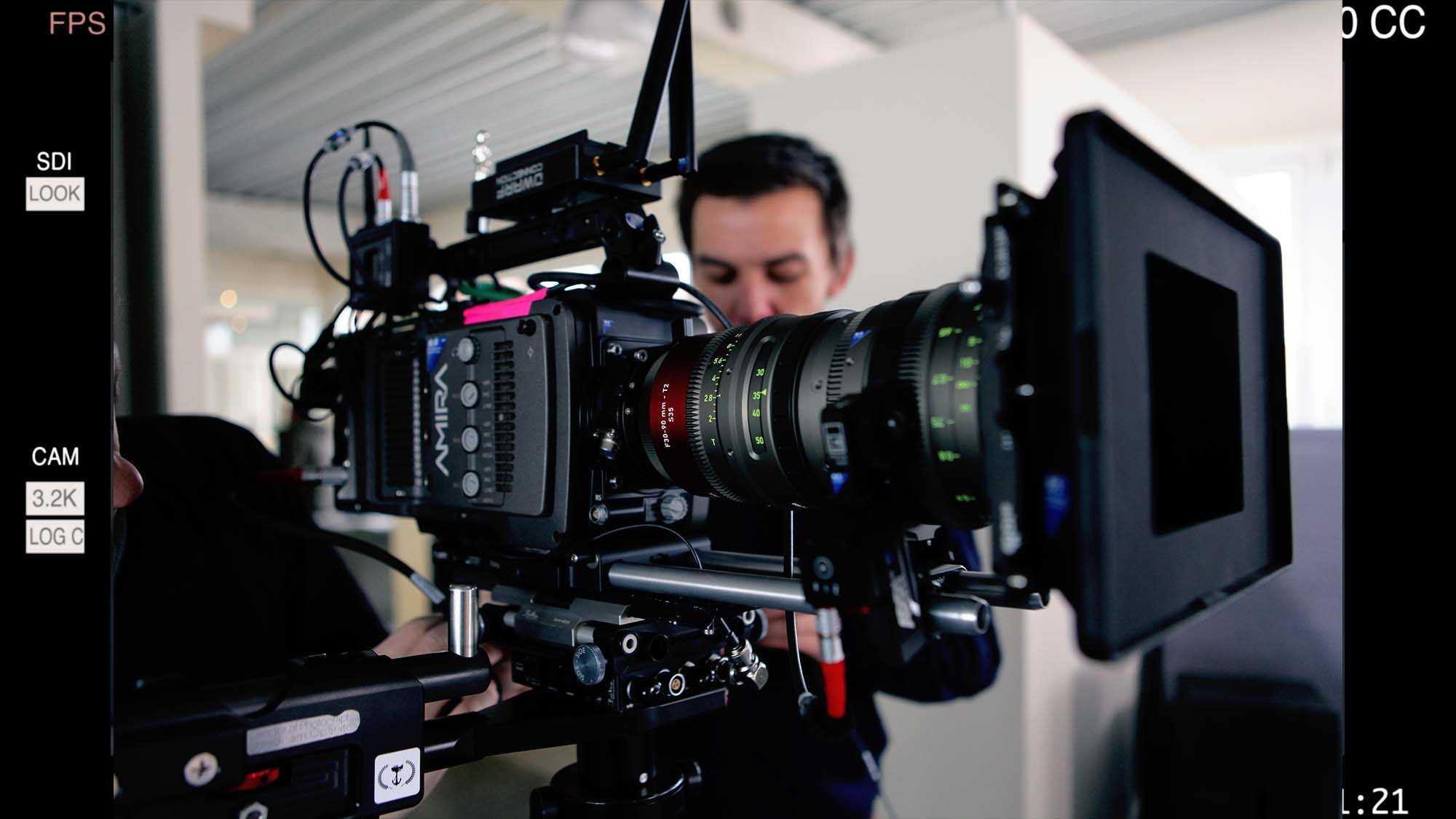 Das Bild zeigt einen Mann der hinter einer Kamera steht. Die Kamera ist seitlich zu sehen. Das Bild dient als Sliderbild für den Portfolioeintrag Yourfone - DRTV Spot von Panda Pictures.