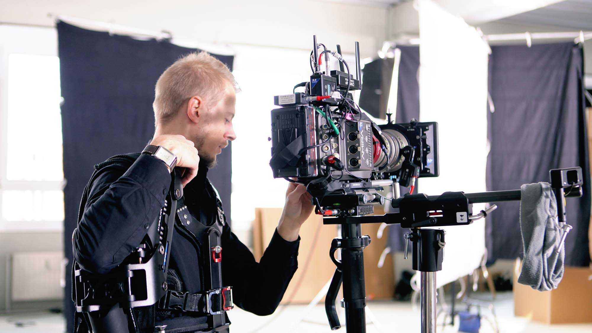 Das Bild zeigt eine Kamera. Vor der Kamera steht ein Mann. Er ist der Kameramann. Er trägt einen Gurt als Halterung um seinen Körper. Er befindet sich in einem Raum. Das Bild dient als Sliderbild für den Portfolioeintrag Yourfone - DRTV Spot von Panda Pictures.