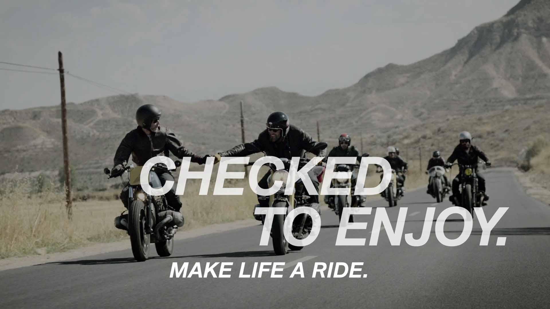 Das Bild zeigt zwei Motorradfahrer die sich gegenseitig eine Faust geben. Im Hintergrund sind Berge und noch weitere Motorradfahrer zu sehen. Das Bild dient als Slider Bild wurde für den Portfolioeintrag BMW - Checked to enjoy von Panda Pictures.