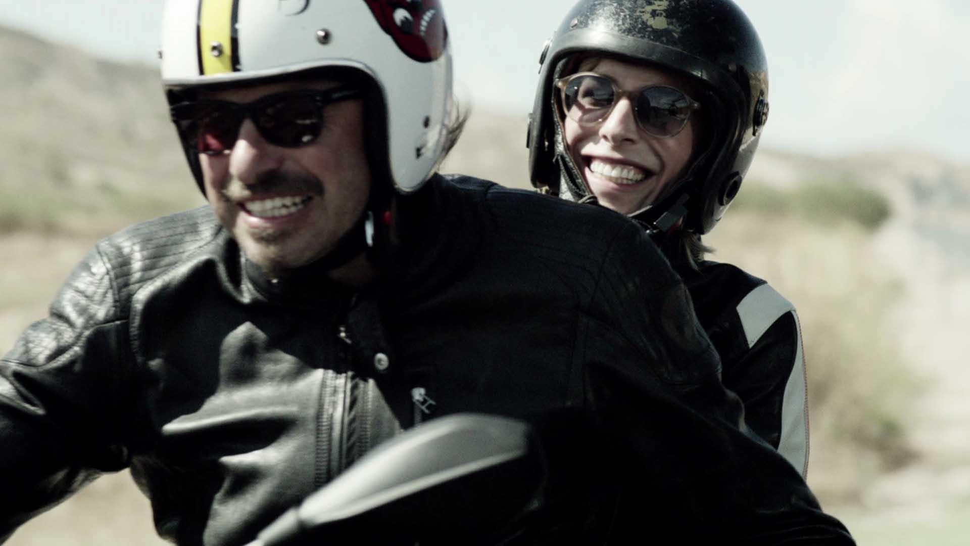 Das Bild zeigt zwei Menschen, einen Mann und eine Frau. Sie lachen und tragen Sonnenbrillen und Motorradhelme. Sie fahren auf einem Motorrad durch eine Landschaft. Das Bild dient als Slider Bild wurde für den Portfolioeintrag BMW - Checked to enjoy von Panda Pictures.