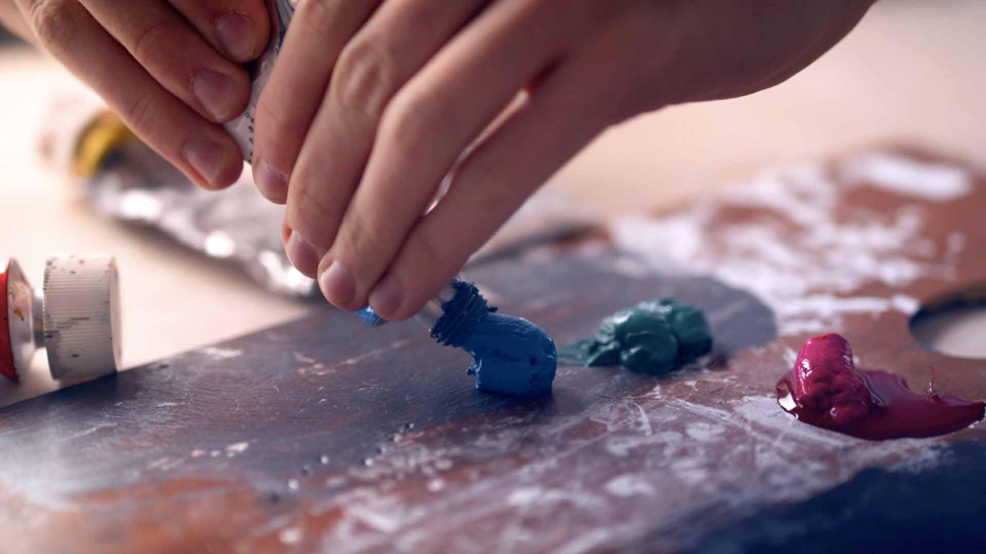 Das Bild zeigt zwei Hände. Diese halten eine Tube mit Farbe welche sie heraus pressen. Die Farbe ist blau und fällt auf ein Stück Holz. Das Bild dient als Making Of Bild für den Portfolioeintrag Bayerischer Volkshochschulverband von Panda Pictures.