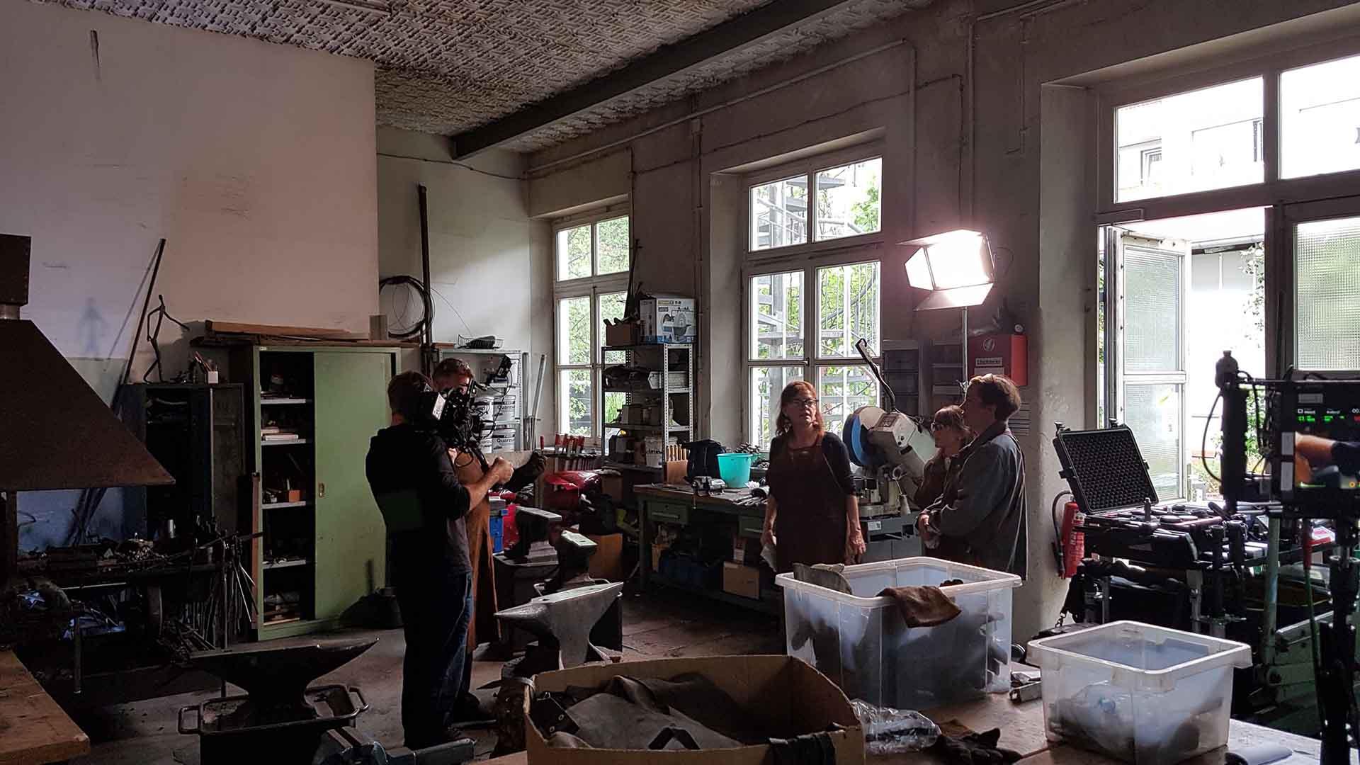 Das Bild zeigt einen Raum der zum Schmieden verwendet wird. Man sieht einen Amboss. Ein Kameramann filmt das geschehen. Das Bild dient als Sliderbild für den Portfolioeintrag Bayerischer Volkshochschulverband von Panda Pictures.