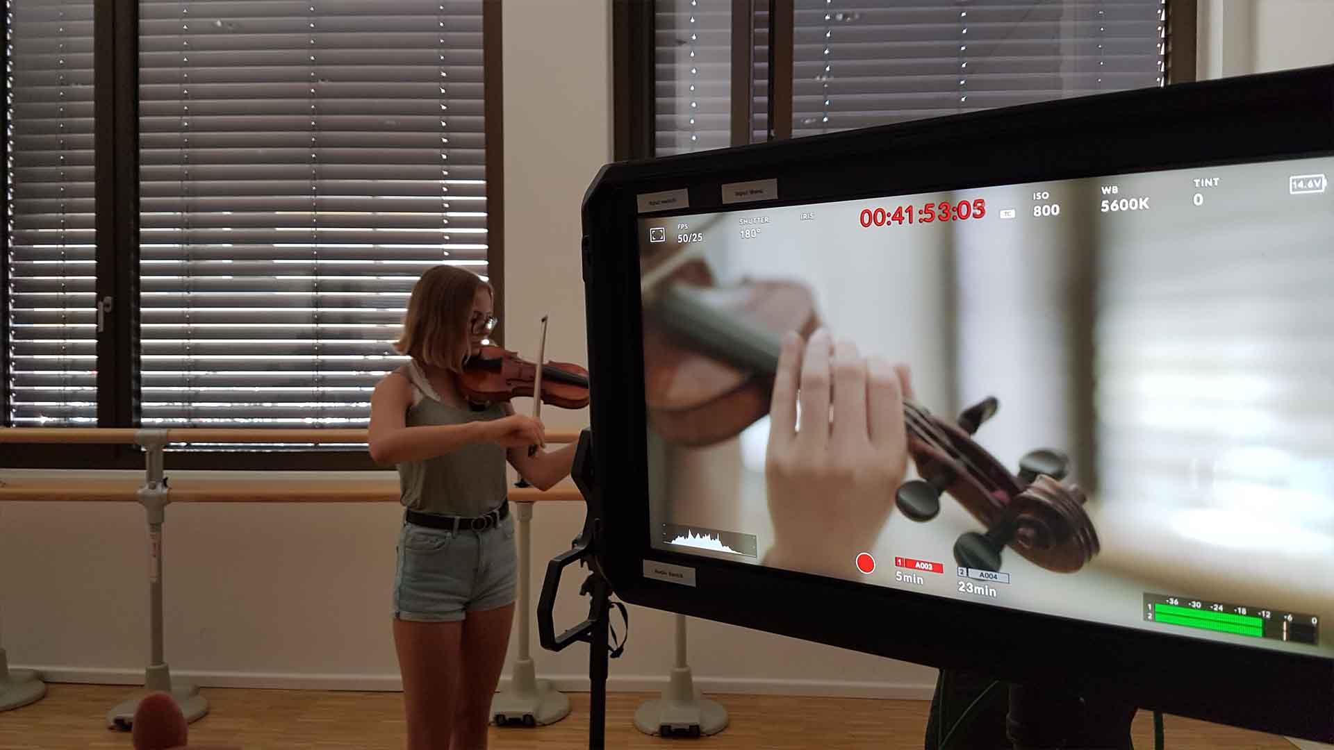 Das Bild zeigt einen Monitor, der mit einer Kamera verbunden ist. Er zeigt das gefilmte. eine Geige. Hinter dem Monitor sieht man die zugehörige Geigerin. Das Bild dient als Sliderbild für den Portfolioeintrag Bayerischer Volkshochschulverband von Panda Pictures.