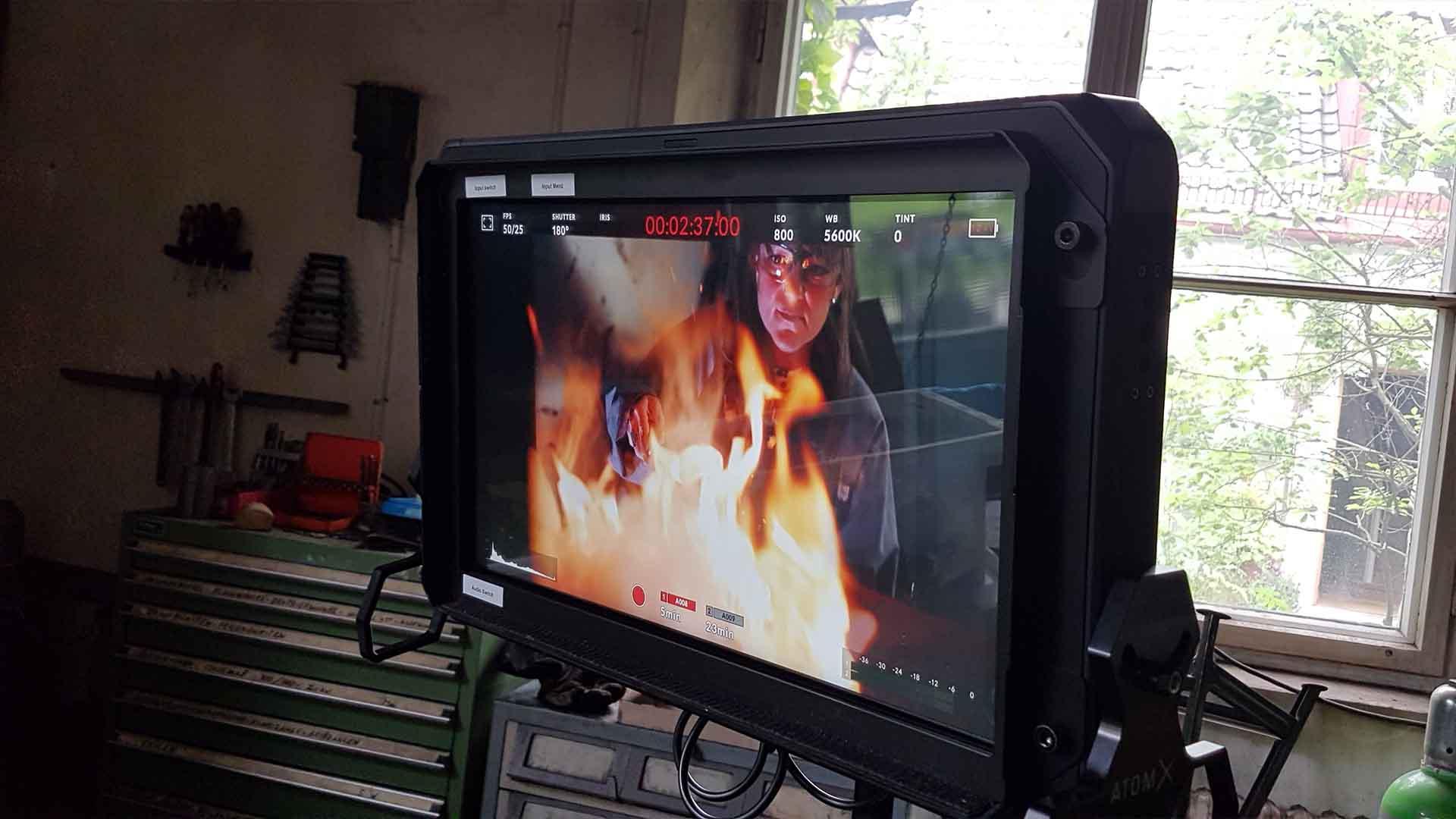Das Bild zeigt einen Monitor, der mit einer Kamera verbunden ist. Auf dem Bildschirm sieht man ein Feuer. Hinter diesem Feuer steht ein Mann, der Schmid. Das Bild dient als Sliderbild für den Portfolioeintrag Bayerischer Volkshochschulverband von Panda Pictures.